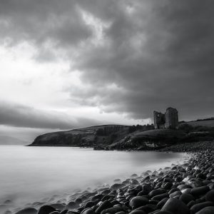 black and white image of a rocky shoreline with an old castle in the background