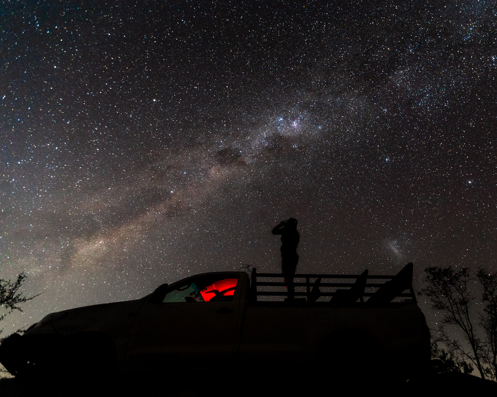 man on truck at night with binoculas. The milky Way is in the background